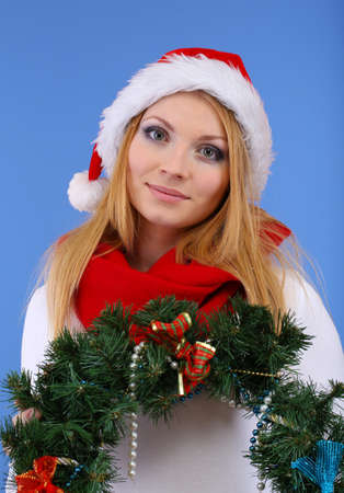Attractive young woman holding Christmas wreath,on blue background photo