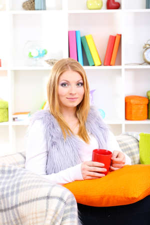 Attractive young woman sitting on sofa, holding cup with hot drink, on home interior background Stock Photo - 17281536