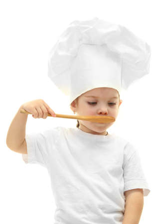 little girl in chefs hat with spoon, isolated on white photo