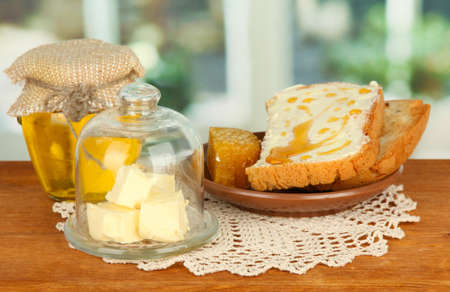 Butter on glass saucer with glass cover and fresh bread,honey, on bright background Stock Photo - 17064156