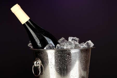 darck: Bottle of wine in ice bucket on darck purple background