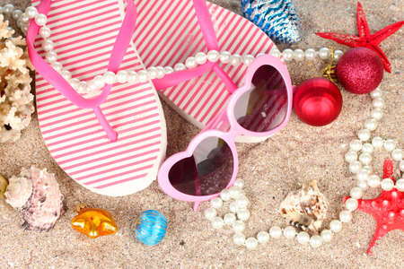 beach happy new year: Christmas balls,seashells andh beach accessories on sand, close-up