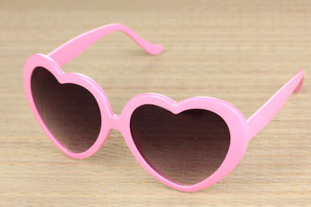 Pink heart-shaped sunglasses on bamboo mat Stock Photo - 17116835