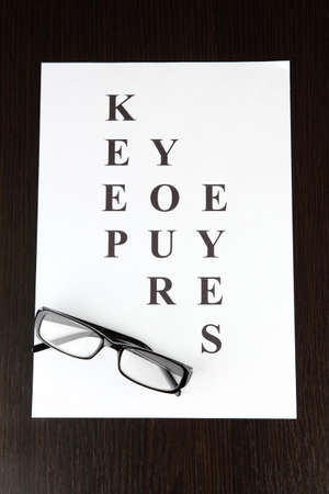 Eyesight test chart with glasses on wooden background close-up Stock Photo - 17117000