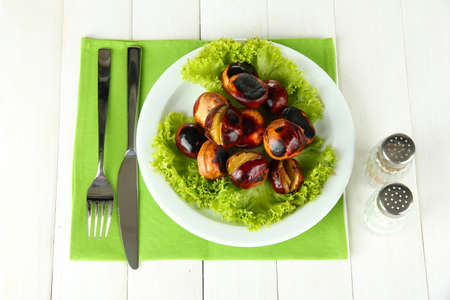 roasted chestnuts with lettuce in the plate on white wooden background Stock Photo - 17117804