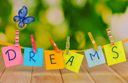 The word Dreams on wooden table on natural background photo