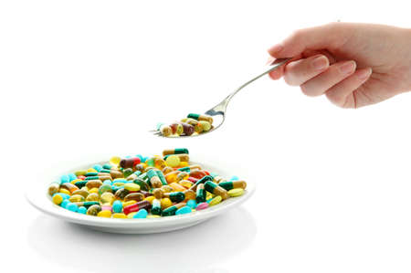 Colorful capsules and pills on plate with spoon in hand, close up photo
