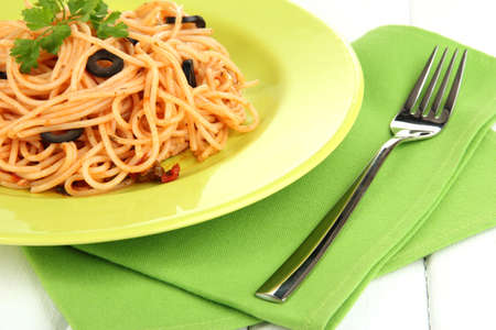 Italian spaghetti in plate on wooden table close-up photo