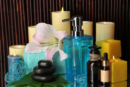 Beautiful spa setting on bamboo background with reflection photo