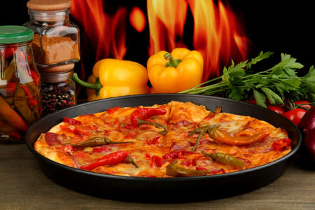 Tasty pepperoni pizza in pan with vegetables on flame background photo