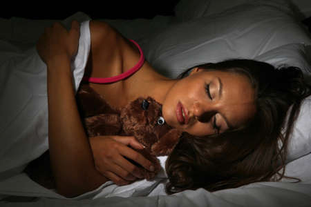 young beautiful woman with fluffy bear sleeping in bed in dark bedroom photo