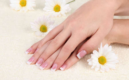 Woman hands with french manicure and flowers on towel photo