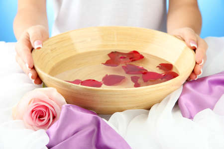 woman hands with wooden bowl of water with petals, on blue background Stock Photo - 17116949