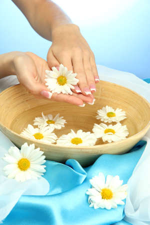 woman hands with wooden bowl of water with flowers, on blue background photo