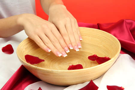 woman hands with wooden bowl of water with petals, on red background Stock Photo - 17117256