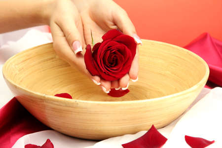 woman hands with wooden bowl of water with petals, on red background photo