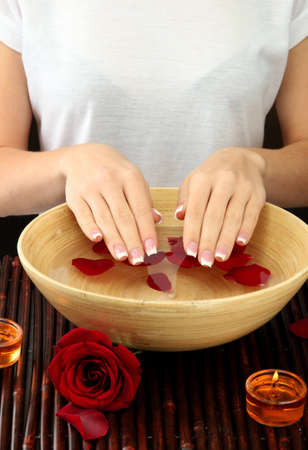 woman hands with wooden bowl of water with petals Stock Photo - 17116921