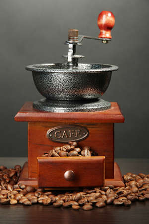 Coffee grinder with coffee beans on grey background photo
