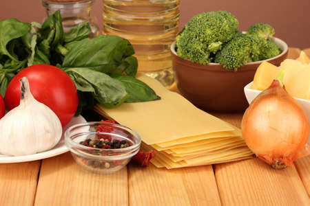 Vegetarian lasagna ingredients on brown background photo