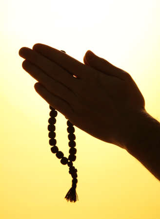 male hands with rosary, on yellow background photo