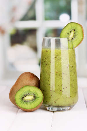 Glass of fresh kiwi juice on wooden table, on window background photo