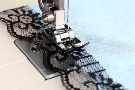 needle lace: Closeup of sewing machine working part with  blue cloth