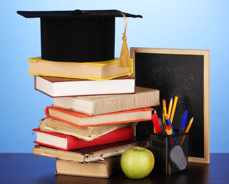 Books and magister cap against school board on wooden table on blue background photo