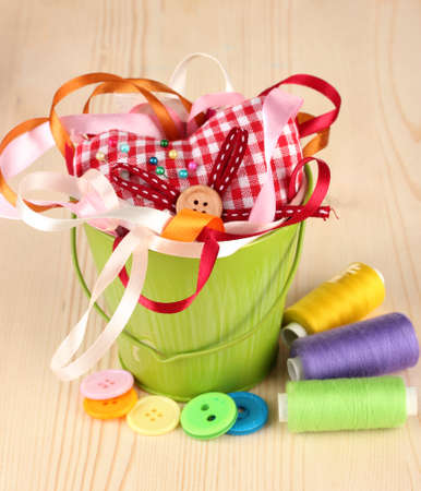 Color bucket with multicolor ribbons and thread on wooden background Stock Photo - 17116669