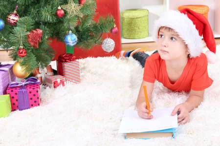 Little boy in Santa hat writes letter to Santa Claus Stock Photo - 17282571