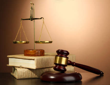 defendant: Golden scales of justice, gavel and books on brown background Stock Photo