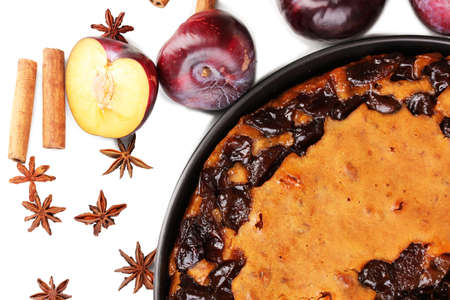 Tasty pie on pan with plums and cinnamon isolated on white Stock Photo - 17119374