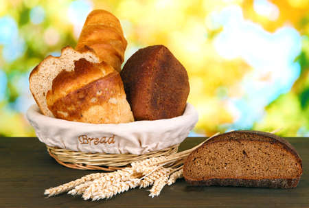 Fresh bread in basket on wooden table on natural background photo