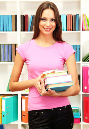 Young attractive female student holding her school books in library Stock Photo - 17281933
