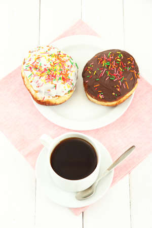 Tasty donuts on color plate on light wooden background photo