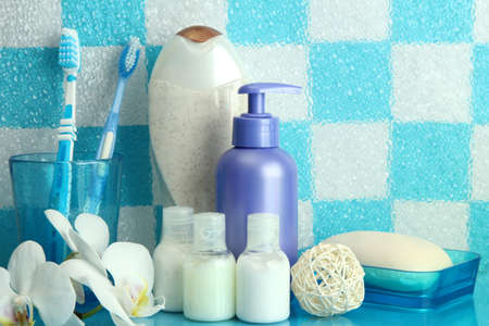 Bath accessories on shelf in bathroom on blue tile wall background photo