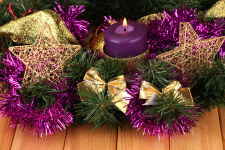 Christmas composition  with candles and decorations in purple and gold colors on wooden background photo