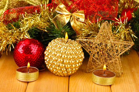 Christmas composition  with candles and decorations in red and gold colors on wooden background photo