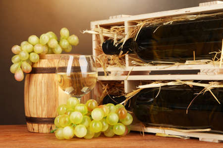 Wooden case with wine bottle, barrel, wineglass and grape on wooden table on brown background Stock Photo - 17117796