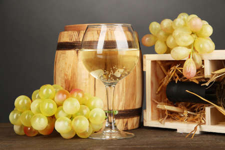 dura: Wooden case with wine bottle, barrel, wineglass and grape on wooden table on grey background Stock Photo