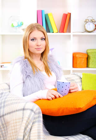 Attractive young woman sitting on sofa, holding cup with hot drink, on home interior background photo