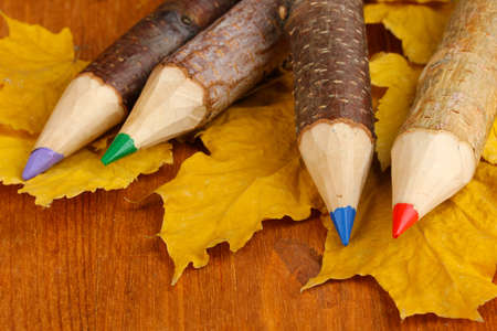 Colorful wooden pencils with autumn leafs on wooden table photo
