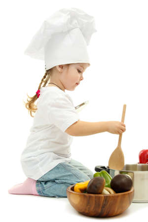 little girl in chef's hat with pan and vegetables, isolated on white photo