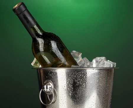 darck: Bottle of wine in ice bucket on darck green background Stock Photo