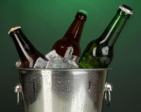 darck: Beer bottles in ice bucket on darck green background Stock Photo