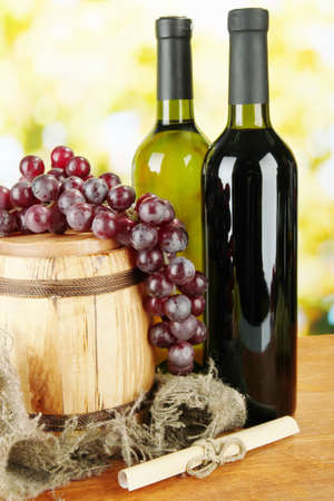 composition of wine and grapes on wooden barrel on bright background photo