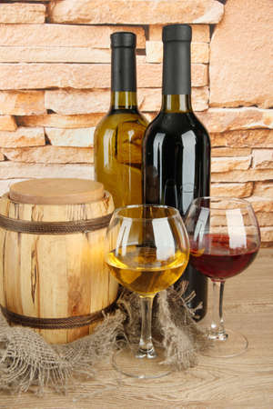 composition of wine and wooden barrel on table on brick wall background photo