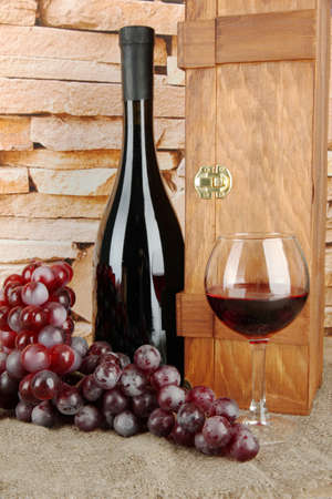 composition of wine,box and grapes on table on brick wall background photo
