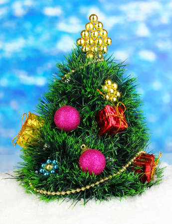 Decorated artificial Christmas Tree on bright background photo