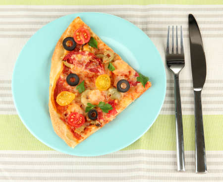 plate with a slice of delicious pizza on tablecloth close-up photo