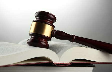 derecho penal: Mazo de madera y libros, sobre fondo gris